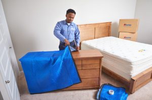 man covering furniture with plastic sheet