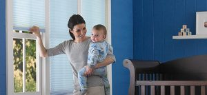mother holding her baby standing near cordless window