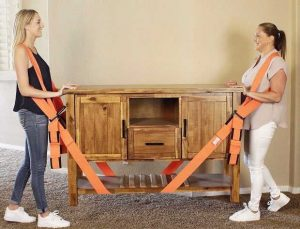 Two women holding drawer with the help of moving straps