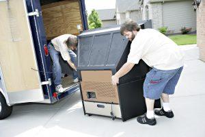two man loading heavy stuff in a van