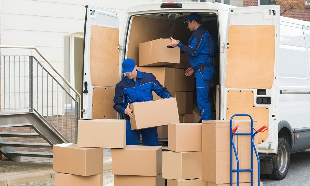two men loading moving boxes in a van